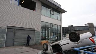 Un mecánico cae con un coche desde la planta alta de un taller